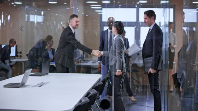 ds business team entering the glass conference room and greeting the other team - деловая встреча стоковые видео и кадры b-roll