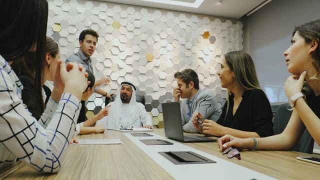ofiste arap işadamı ile iş toplantısı yapan iş ekibi - abu dhabi stok videoları ve detay görüntü çekimi
