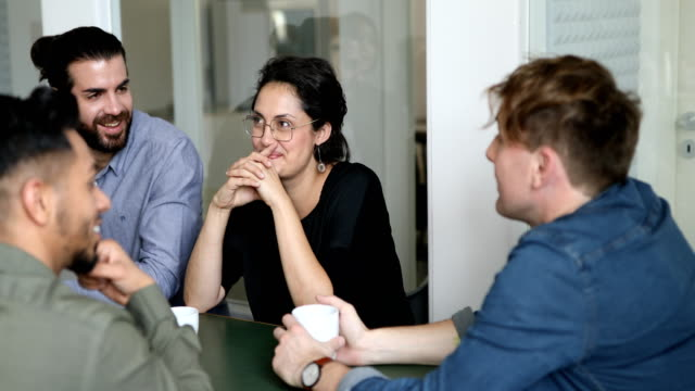 Business team having fun conversation during coffee break at office Business team having fun conversation during coffee break at office. Multi-ethnic group of men and women sitting at cafeteria and talking. employee engagement stock videos & royalty-free footage