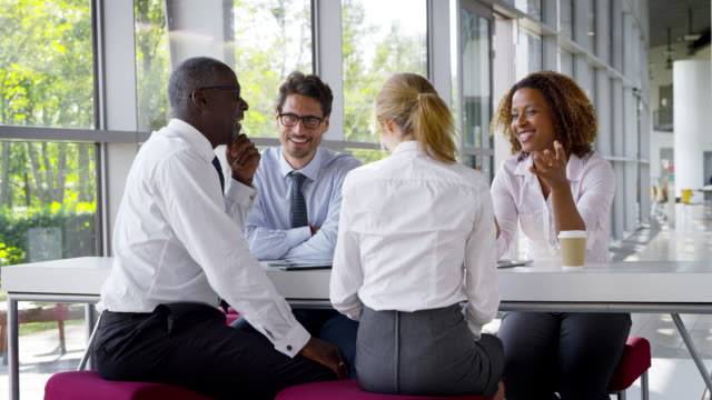 stockvideo's en b-roll-footage met business team met vergadering rond tafel in moderne kantoor - vier personen