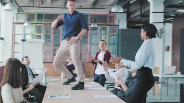 Business team holds a meeting at a large table. The manager gets up on the table and starts to dance. Employees dance with him and celebrate success. Office life. Workers celebrate. Co-working video