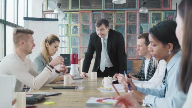 ビジネスチームは大きなテーブルで会議を開きます。マネージャーは椅子から立ち上がり、メガホンを手に取り、スタッフに向けて誓い、叫びます。オフィスライフ。クリエイティブなイン� ビデオ