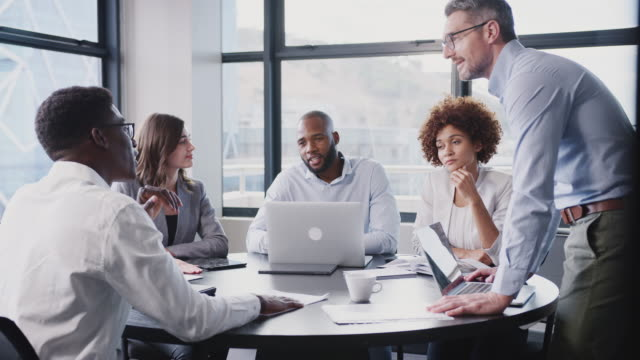 Business team in discussion at a table in meeting room, middle aged white businessman standing Business team in discussion at a table in meeting room, middle aged white businessman standing business meeting stock videos & royalty-free footage