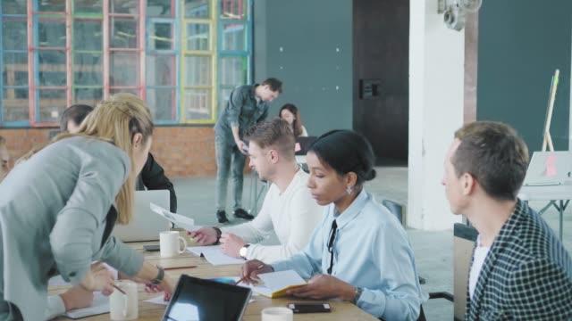 Ein Business-Team diskutiert ein Projekt an einem großen Bürotisch. Kreative Büro-Interieur. Co-Working. Büroangestellte – Video
