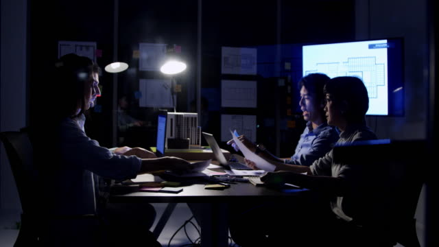 stockvideo's en b-roll-footage met team zakenvergadering in kantoor 's nachts. werken late concept. - omgeving
