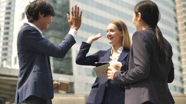 ビジネスチームの人々は、お祝いの成功に高いハイタッチ - グローバル点の映像素材/bロール