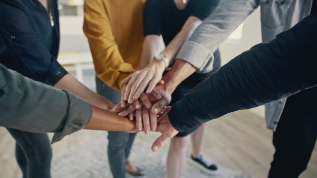 Business team showing unity Multi-ethnic businesspeople putting their hands on top of each other and clapping. Business team making a stack of hands showing unity. employee stock videos & royalty-free footage