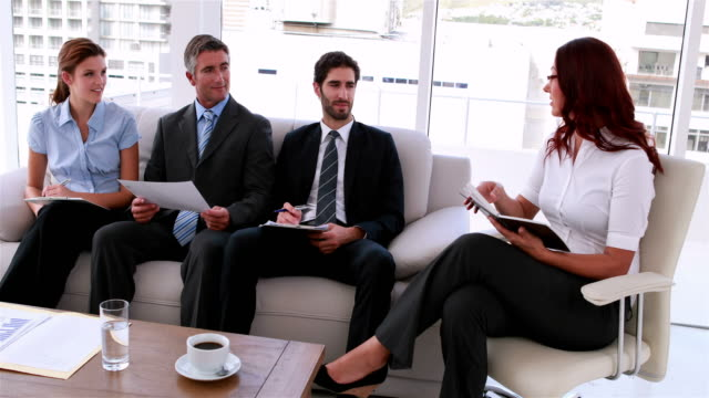 Business team sitting on couch having a meeting video