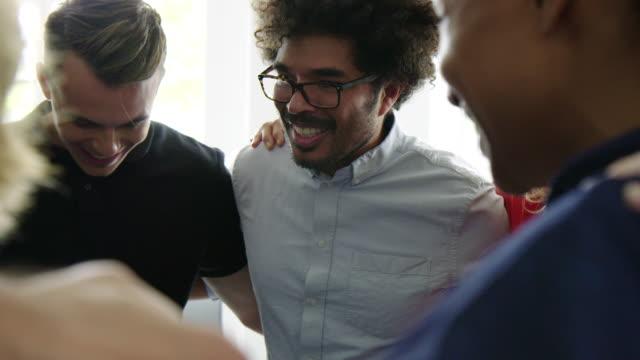 vídeos de stock e filmes b-roll de business team smiling in a huddle - funcionamento em rede