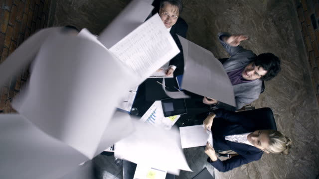 Business team throws documents and papers into air video