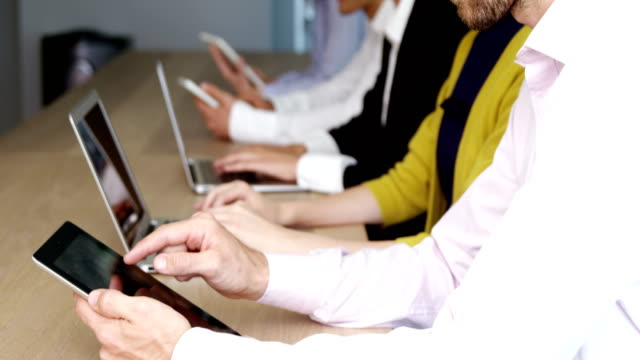 Business team using digital tablet and laptop in conference room video