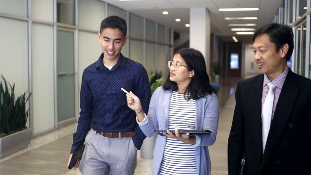 vídeos de stock e filmes b-roll de business team walking down a hallway - etnia filipina