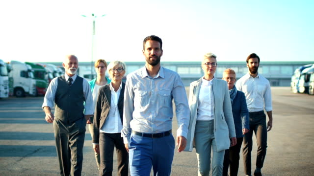 Business team walking outdoors in slow motion.