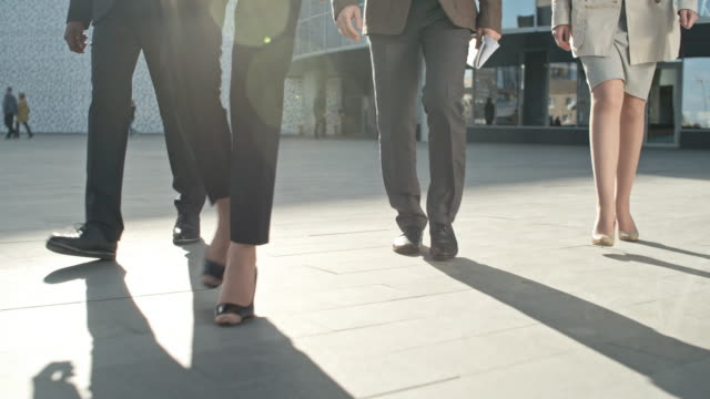 Business Team Walking Legs of four business people walking on the pavement in front of office building stepping stock videos & royalty-free footage