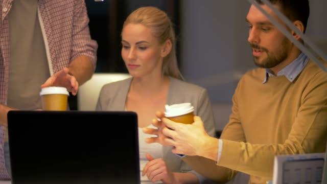 vídeos de stock, filmes e b-roll de equipe de negócios com computador portátil e café trabalhando no escritório de noite - sul europeu