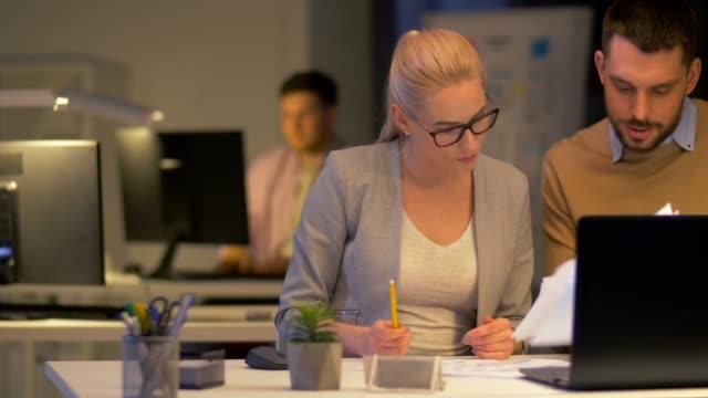 vídeos de stock, filmes e b-roll de equipe de negócios com laptop trabalhando no escritório de noite - sul europeu