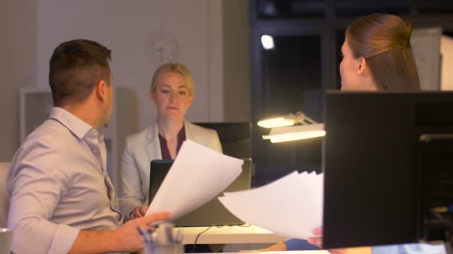 vídeos de stock, filmes e b-roll de equipe de negócios com os papéis trabalhando até tarde no escritório - sul europeu