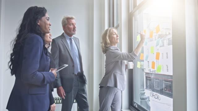Business-Team schreiben Ideen auf Haftnotizen im Büro – Video