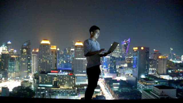 business using laptop and digital tablet at skyscaper background - cultura orientale video stock e b–roll