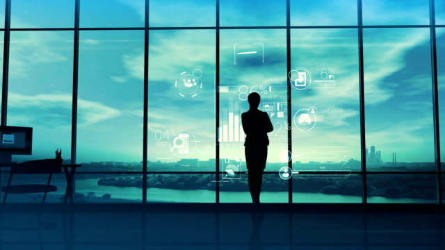 Business woman and corporate infographics Silhouette of a woman in a huge office in front of large windows viewing corporate infographics. silhouette people stock videos & royalty-free footage