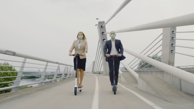 SLO MO Business woman and man in surgical masks riding electric scooters to work Slow motion shot of a business man and woman wearing surgical masks while riding electric scooters on a bridge to work. Shoot in 8K resolution. alternative fuel vehicle videos stock videos & royalty-free footage