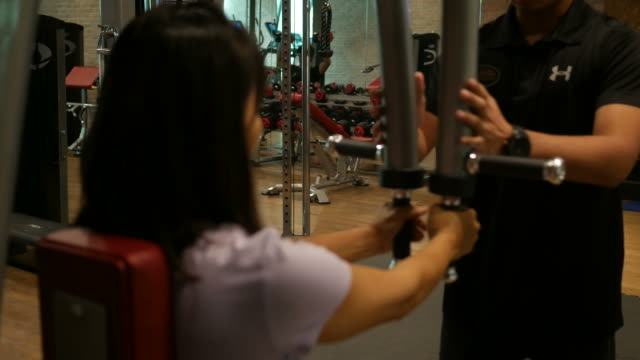 Business woman and personal trainer in gym video