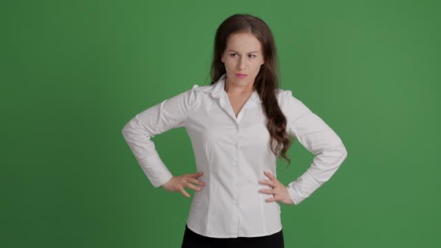 mujer de negocios enojado mira y amenaza con el dedo en fondo verde - vídeo