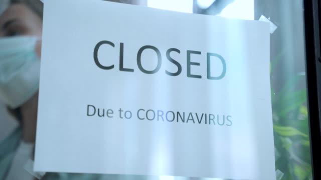 donna d'affari che allega un cartello chiuso aziendale all'ingresso del negozio a causa della crisi finanziaria dovuta all'epidemia di coronavirus covid-19 in tutto il mondo - completo video stock e b–roll