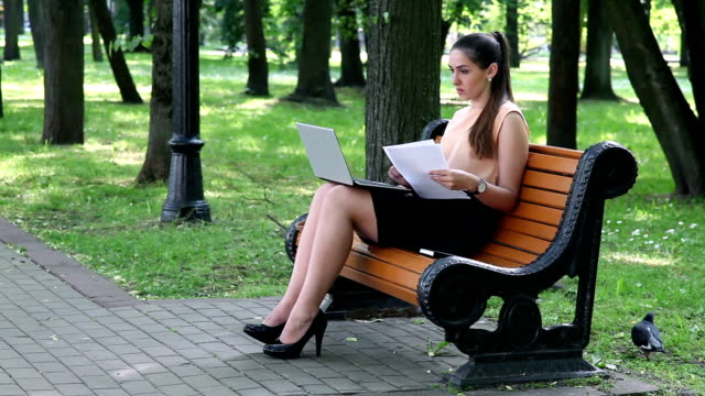 Business woman comparing data from laptop screen with printed document video