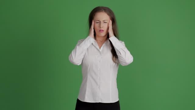 mujer de negocios experimenta un dolor de cabeza sobre un fondo verde - vídeo