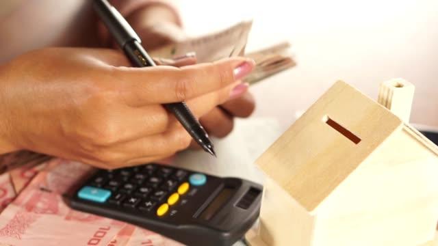 business kvinna hand räkna pengar pappersvaluta med att spara räkenskapsbok, husmodell och kalkylator på skrivbord - lön bildbanksvideor och videomaterial från bakom kulisserna