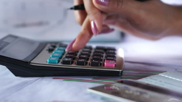 business woman hand counting on calculator for finance ,investment and payment concept background business woman hand counting on calculator for finance ,investment and payment concept background with credit card and chart on desk loan stock videos & royalty-free footage