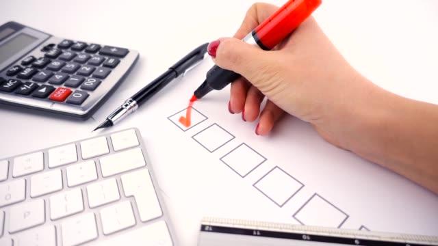 video donna d'affari riempie la lista di controllo con pennarello in ufficio, rallentatore - to do list video stock e b–roll