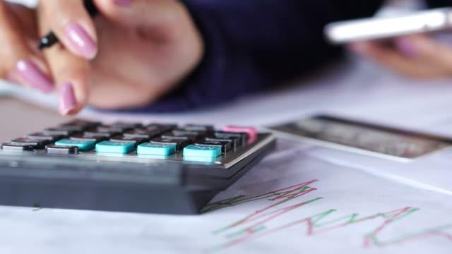 vídeos y material grabado en eventos de stock de mano de mujer de negocios de la escritura y el cálculo de sus gastos mensuales con desenfoque de fondo tarjetas de crédito, teléfono inteligente - gerente de cuentas