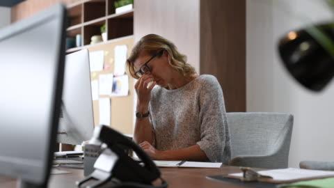 vidéos et rushes de femme d'affaires ayant des maux de tête au bureau - travailler