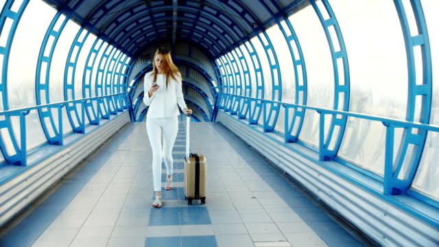 Business woman in a white suit with travel bag. There is a tunnel of glass, looking at smartphone screen