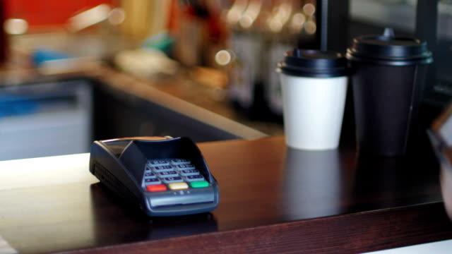 business-frau in café zahlt den preis durch den einsatz ein intelligenten uhren und terminal - kleine uhr stock-videos und b-roll-filmmaterial