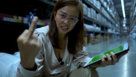 vidéos et rushes de femme d'affaires en stocker la vérification de l'inventaire sur tablette numérique, grave émotion, montrant le doigt moyen - marchandise