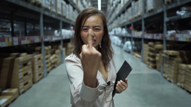donna d'affari in negozio che controlla l'inventario su tablet digitale, emozione seria, mostrando il dito medio - dirigente video stock e b–roll