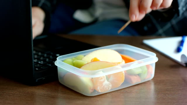 Business woman in suit has working on laptop and eating a healthy fruit snack from lunch box