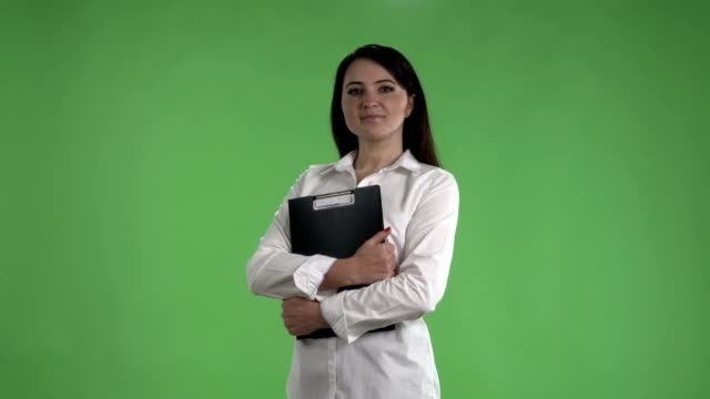 Business woman in white shirt with folder for papers against a green screen - video