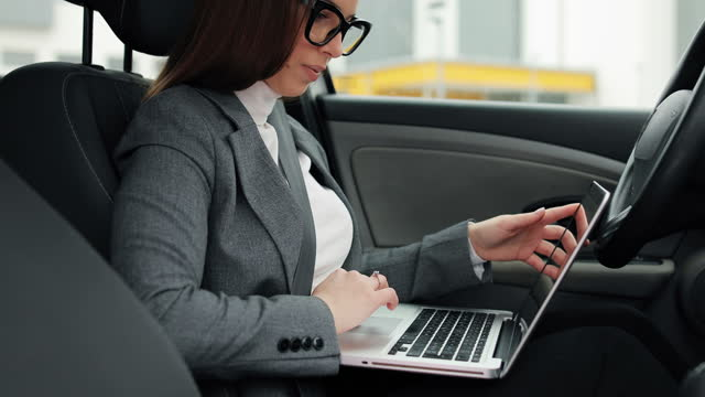 business woman is sitting in her car in the driver's seat and using a laptop video