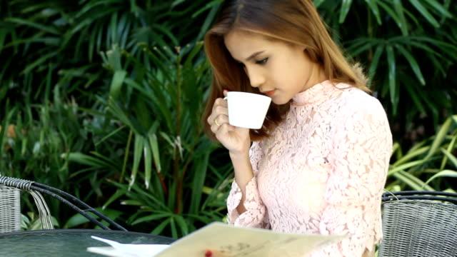 女性実業家は仕事やコーヒーを飲みながらコーヒーカフェ」の屋外 ビデオ