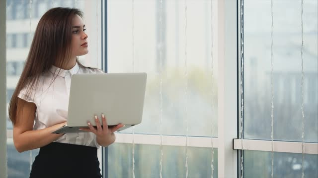 Business woman is working with a grey laptop, isolated on light panoramic blurred background. Copy space. Close up. 4K. Concept business and negotiations. White collar. Copy space. Close up. Lady is smiling, because she came up with an idea. 4K. musical theater stock videos & royalty-free footage