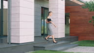 istock Business woman leaving office building with laptop. 1169447424