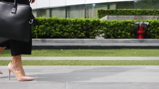 i̇ş kadını bacaklar yüksek topuk ayakkabı çanta ile yürüyüş - uzun adımlarla yürümek stok videoları ve detay görüntü çekimi