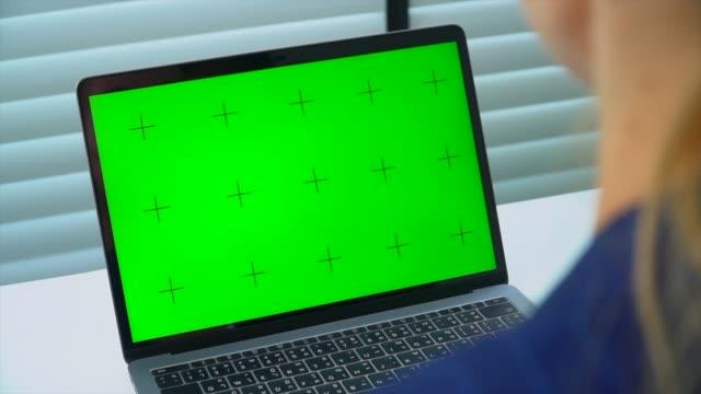 vídeos de stock, filmes e b-roll de mulher de negócio que olha o portátil com tela verde - fundo verde
