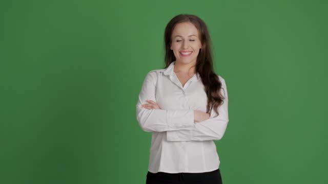 mujer de negocios mirando a la cámara con una sonrisa y las manos cruzadas sobre un fondo verde - vídeo