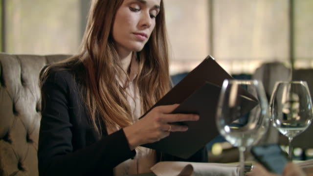 Business woman looking menu in restaurant. Businesswoman choosing lunch
