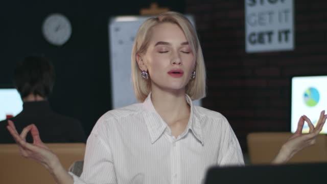 donna d'affari meditando nello yoga posa tavolo da front computer in ufficio notturno - posizione corretta video stock e b–roll